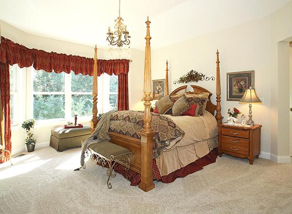 Кровать со столбиками в спальне в стиле кантри План 1-этажного дома с красивой крышей