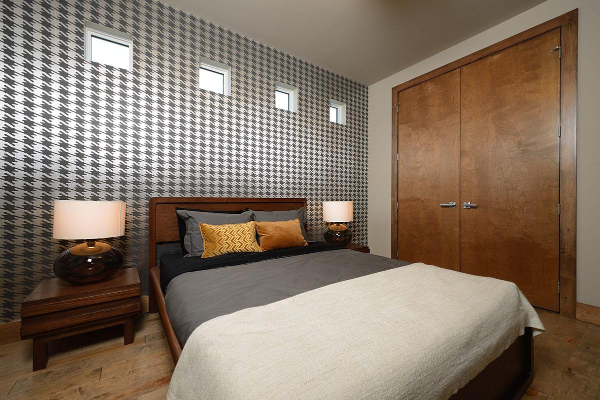 Спальня с белыми стенами и черно-белыми обоями на одной стене