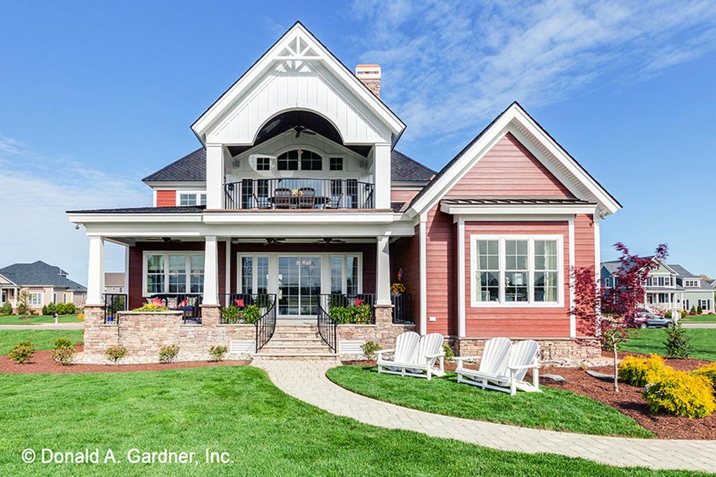Красивый двухэтажный дом в американском стиле с 5 спальнями и гаражом. Фасад облицован камнем. В гостиной второй свет. Сзади дома веранда и патио.