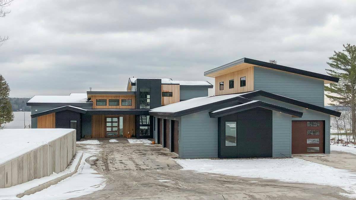 Интересный проект двухэтажного каркасного дома П-образной формы из несъемной опалубки в современном стиле площадью 298 кв.м с гаражом на 2 машины и с 4 спальнями. В большой спальне есть ванная и гардеробная комната.